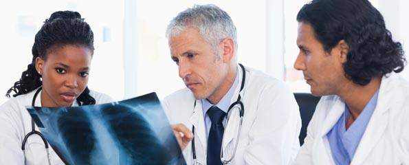 Mature doctor with two co-workers working on an x-ray of lungs