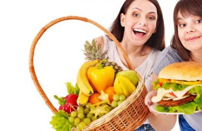 Women choosing between fruit and hamburger