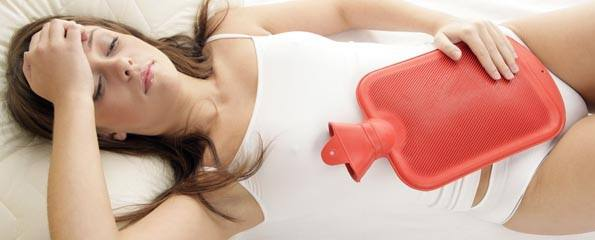 Woman with hot water bottle on stomach